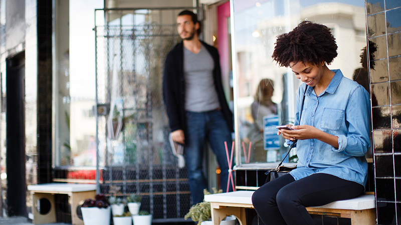 Woman sitting on a bench outside of a business while on her mobile phone.